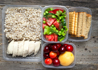 Healthy food, cooked in containers, pearl barley porridge with chicken breast, vegetables, fruits.