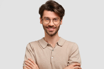 Studio portrait of happy delighted attractive male keeps hands crossed, dressed in casual outfit, looks joyfully, being self confident in success, isolated over white background. Happiness concept