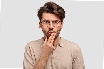 Horizontal shot of emotive puzzled angry European male holds chin and looks in bewilderment, has serious expression, doesn`t understand something, stands against white background. Emotions concept