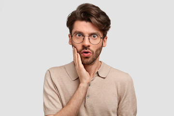 Indoor shot of bearded serious male with scared expression, touches cheek, has dark stubble, dressed in casual outfit, stands against white background. People, reaction, lifestyle, emotions concept