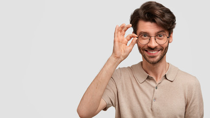 Wall Mural - Horizontal shot of cheerful pleased unshaven male keeps hand on rim of spectacles, dressed casually, has positive expression, glad to recieve praise from someone, isolated on white wall, blank space