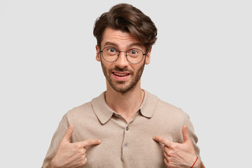 Portrait of indignant Caucasian young male indicates at himself, puzzled to be chosen for presenting project work, wears spectacles, isolated over white stuido wall. Bearded guy gestures indoor