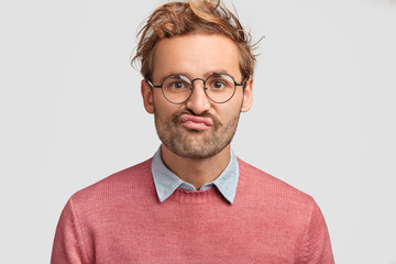 Puzzled displeased male curves lips, looks doubtfully into camera, feels hesitation, dressed in pink sweater, has curly hair, poses against white background. Discontent Caucasian man indoor.