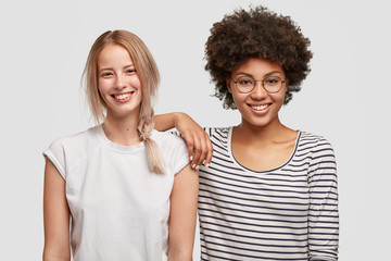 Multiethnic friendship concept. Cheerful European and African women in good mood, happy to meet after long departure. Positive light haired female satisfied to meet with foreigner, spend free time