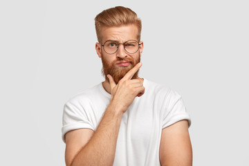 Cool male hipster with thick ginger hair, holds chin, blinks with eye, has fashionable hairdo, dressed casually, stands against white background, feels confident and self assured. Facial expressions