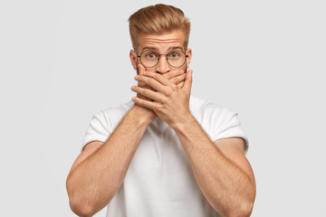 Indoor shot of attractive young male with trendy haircut, covers mouth, being mute, has surprised expression, dressed casually, isolated over white background. Scared hipster expresses fear.