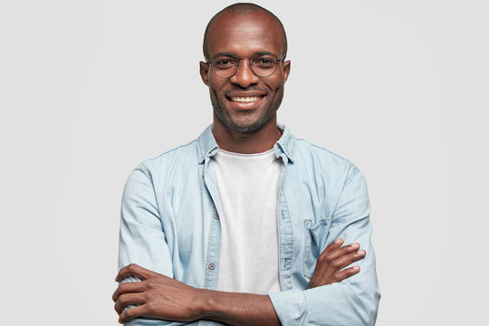 Horizontal shot of prosperous businessman keeps hands crossed, has satisfied expression, looks joyfully at camera, glad to achieve success, dressed in jean jacket, isolated over white background