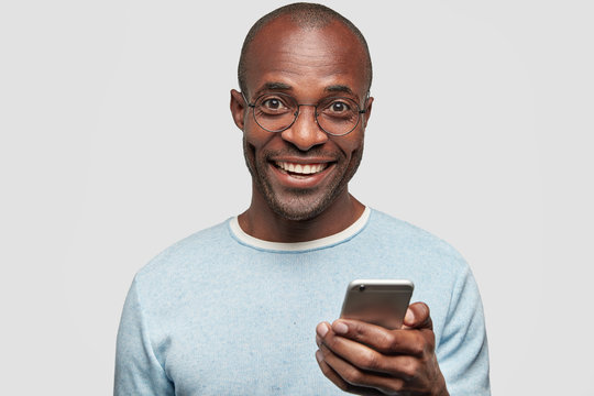 Positive African American male with broad smile, holds modern cell phone, types text message and feedback, surfes social networks, rejoices high speed interent connection, dressed in blue sweater