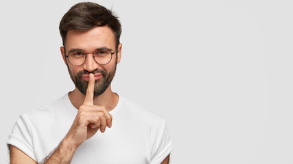 Cheerful mysterious bearded male with dark hair and stubble, makes silence gesture, tells privare information, shares good news with friend, dressed in white t shirt. Monochrome. Secrecy concept