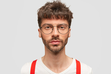 Portrait of serious attractive male student in eyewear, dressed elegantly, comes for passing exam, being self confident in his knowledge, poses against white background. People and confidence concept