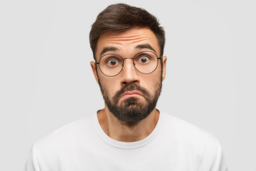Doubtful bearded male purses lips with hesitation, stares at camera with scared expression, feels cluless while recieves unexpected offer from friend, isolated over white background. Facial expression