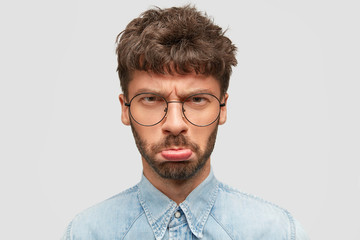 Gloomy Caucasian male with stubble purses lips and looks in displeasure at camera, feels offended after hearing bad words addressed to him, wears denim shirt, poses against white studio wall