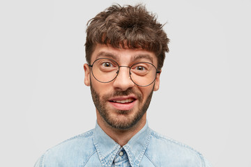 Photo of funny male with stubble, has indecisive and curious look, frowns face, looks directly at camera, dressed in denim shirt, isolated over white background. People and facial expressions concept