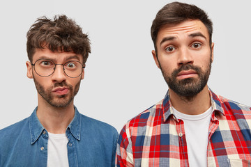 Two bearded male journalists have puzzled expressions, work on creating article, look at camera with bewilderment, dressed in fashionable shirts, stand next to each other, isolated over white wall