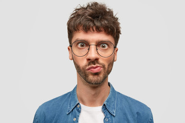 Headshot of puzzled bearded young man looks in wonderment, curves lips, has widely opened eyes, dark wavy hair, recieves unexpected news, thinks over something, stands against white studio wall