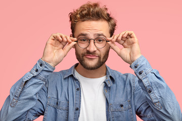 Funny unshaven male has thick beard, keeps both hands on rim of glasses, has curious look while listens something interesting, dressed in denim shirt, isolated over pink background. Facial expressions