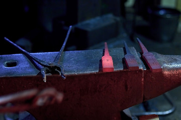 Hot steel parts and forge tongs on the anvil at the forge