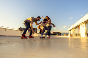 Three friends amuse on rooftop with skateboard. Young and careless friends having fun concept.