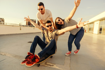 Young Adult Friends Amuse On Balcony At The Top Of The Building. Young and careless friends having fun concept.