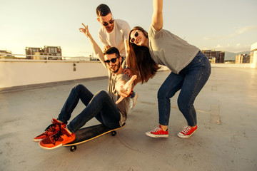 PORTRAIT OF A FRIENDS WHILE DRIVING SKATEBOARD ON BALCONY. Young and careless friends having fun concept.