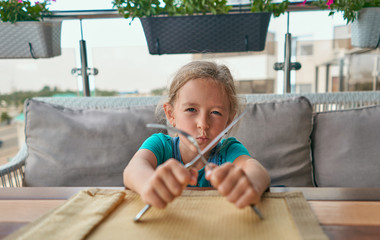 child with a knife and fork in the restaurant