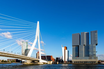 Cityscape of the Dutch city Rotterdam with high rise buildings in the financial district and port area with the Erasmus bridge seen from the water against a blue sky with fluffy clouds