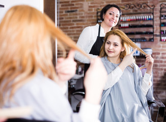 Woman 25-30 years old is showing to haircutter at what length to cut hair.