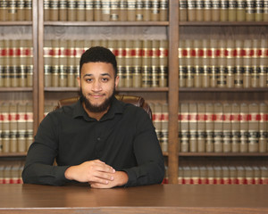 Portrait of a biracial multiethnic young man.  Portrait of a lawyer in law office.