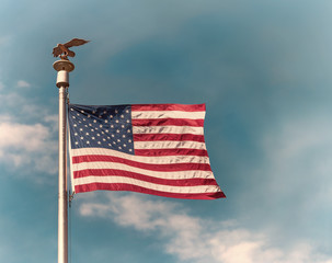 American flag on pole waving in the wind against blue sky and white clouds background. Vintage toned.