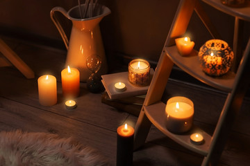 Wooden stand and burning candles indoors
