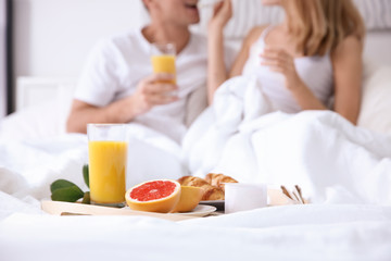 Tray with healthy breakfast on bed of young happy couple