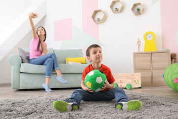 Little boy playing with ball at home while his nanny is taking selfie