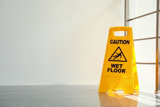 Safety sign with phrase Caution wet floor, indoors. Cleaning service