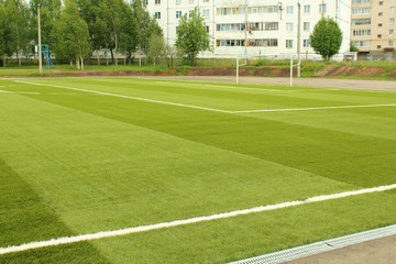Green artificial football field. The school stadium. Background.