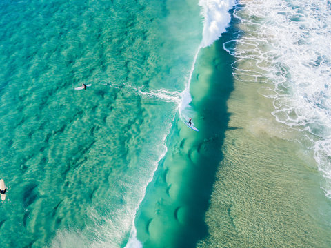 An aerial view of surfer riding a wave waiting at the beach on the Gold Coast in Queensland Australia