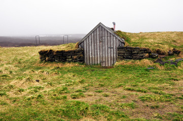 a small wooden house in the field of Iceland covered with moss