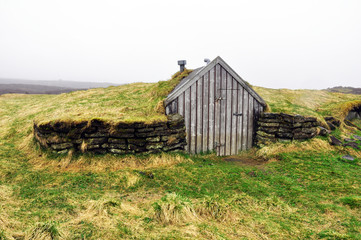 small wooden house for shepherd in Iceland covered with moss