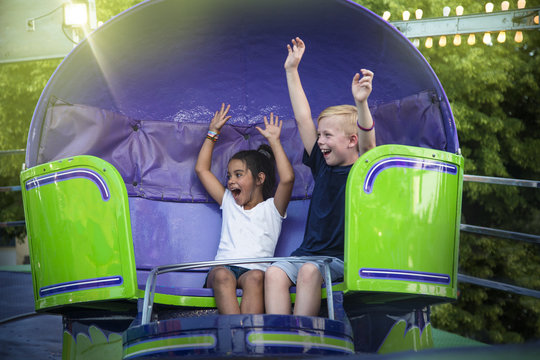 Two screaming Kids enjoying a fun summer amusement park ride. Arms raised and laughing as they twirl around