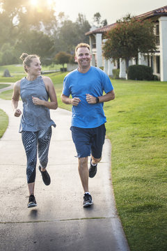 Beautiful woman and mature man jogging together outdoors along a pathway at a city park. Happy and smiling as they run along the path during sunset on a warm summer day
