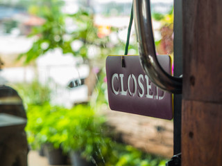 Closed sign board hanging on glass door