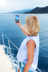 Beautiful woman taking photo on sailboat using smart phone technology for social media in ocean on luxury lifestyle adventure travel vacation. travel and active lifestyle concept