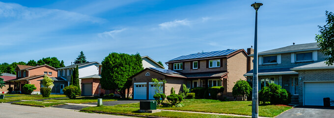 Fototapeta Panorama of a row of residential houses along a street, one with solar panels on the roof obraz