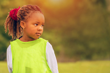 A close portrait of a young African girl under sunset