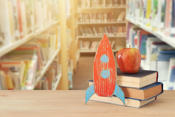 Back to school concept. rocket and books in front of blurry Library background.