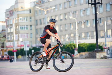 Athletic strong man cyclist posing in professional cycling garment on bicycle in front of city building. Sportsman exercising outdoors, rest after working day. Concept of healthy sporty lifestyle
