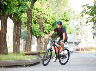 Athletic guy bicyclist in cycling clothes and protective gear riding on bicycle along empty city streets, green trees around. Sportsman performing morning outdoor exercise and training.