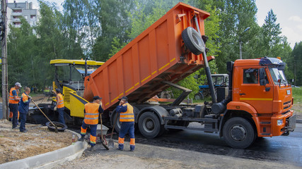 Repair works on laying the asphalt surface on a city street. The dump truck unloads asphalt in paver and workers