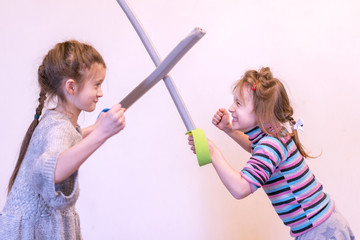 Two little girls are fighting on swords. toned
