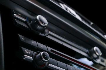 Modern Luxury sport car inside. Interior of prestige car. Black Leather. Car detailing. Dashboard. Media, climate and navigation control buttons. Sound system. Modern car interior details