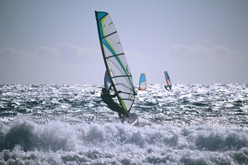 Windsurfers at the Atlantic ocean glistening in the sun with shorebreak in front